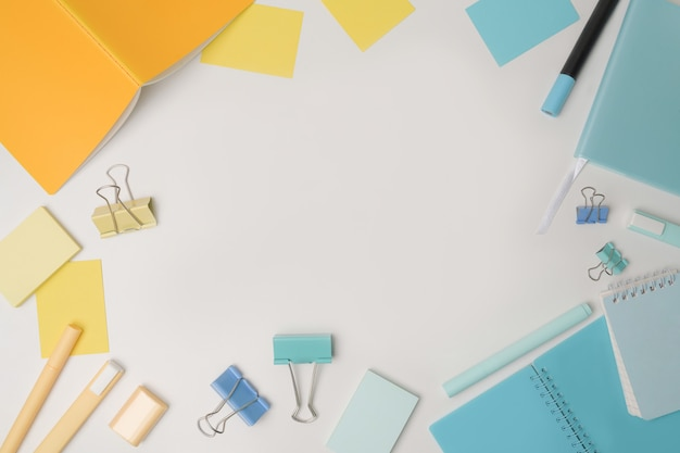 Top view colorful notebooks and stationery on white background.