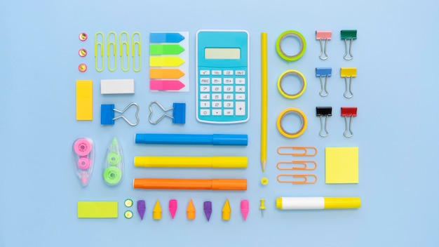 Top view of colorful office stationery with calculator and paper clips