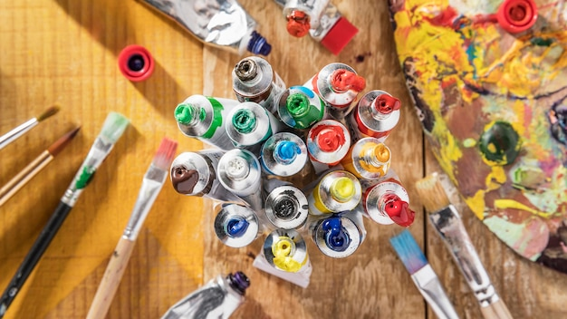 Top view of colorful paint tubes with paint brushes