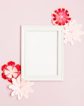 Top view of colorful paper flowers and frame
