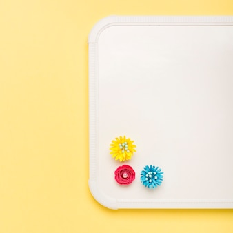 Top view of colorful paper flowers on whiteboard