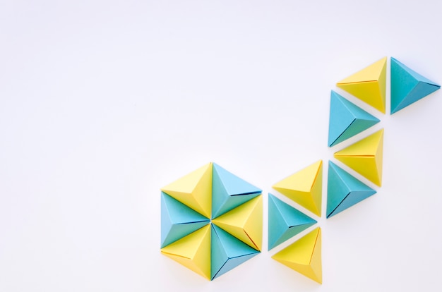 Top view of colorful paper pyramids with copy space