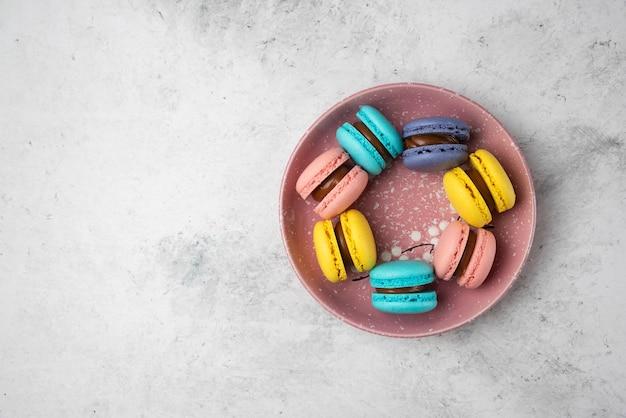 Vista dall'alto di macarons pastello colorati su sfondo bianco.