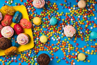 Top view colorful pastries surrounded by bonbon