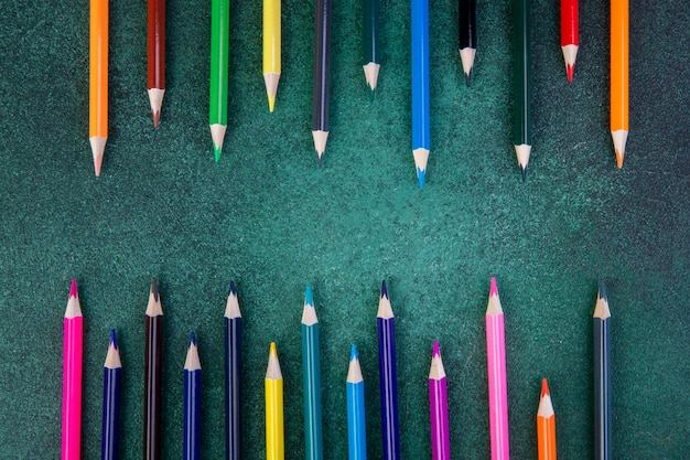 Top view colorful pencils on a green background
