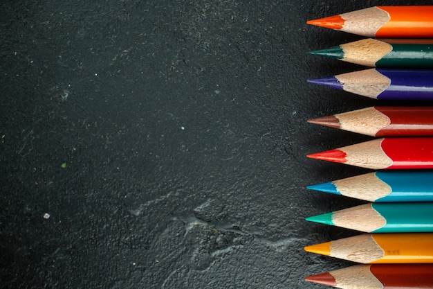 Top view colorful pencils lined on dark background