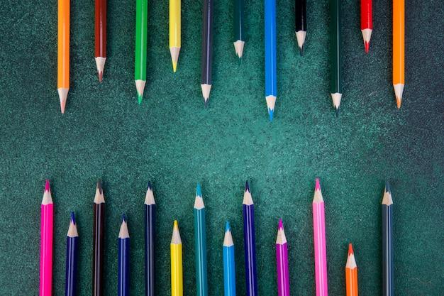 緑の背景に平面図カラフルな鉛筆