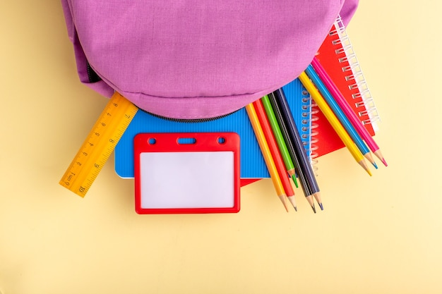 Вид сверху красочные карандаши с тетрадями и фиолетовой сумкой на светло-желтой парте школа фломастер карандаш книга блокнот
