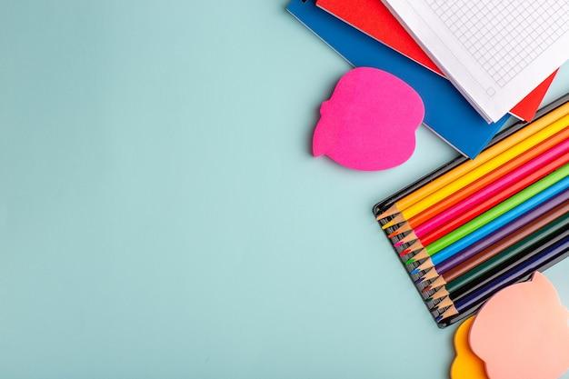 青い壁の色のペンの学校の子供たちのコピーブックとトップビューのカラフルな鉛筆