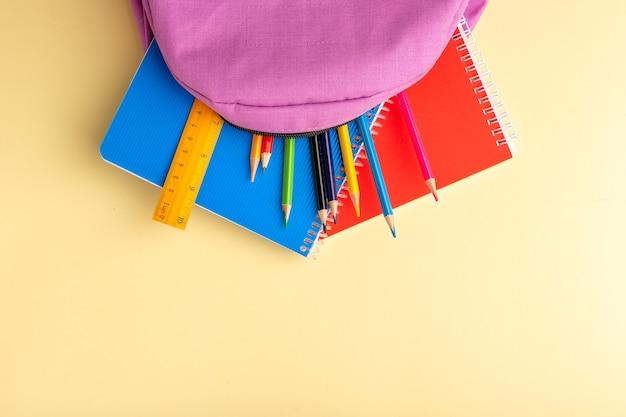 Vista dall'alto matite colorate con quaderni e borsa viola sul blocco note del libro della matita della penna del feltro della scuola della scrivania giallo chiaro