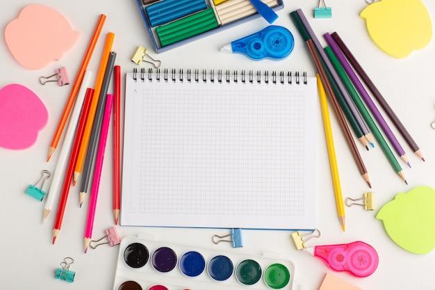 Вид сверху красочные карандаши с красками, блокнот и наклейки на белом столе, искусство рисования цветной краской