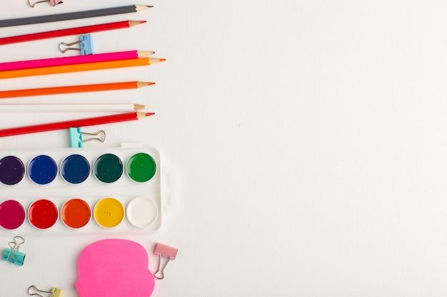 平面図のカラフルな鉛筆と白い机の上のペンキアート描画カラーペイント