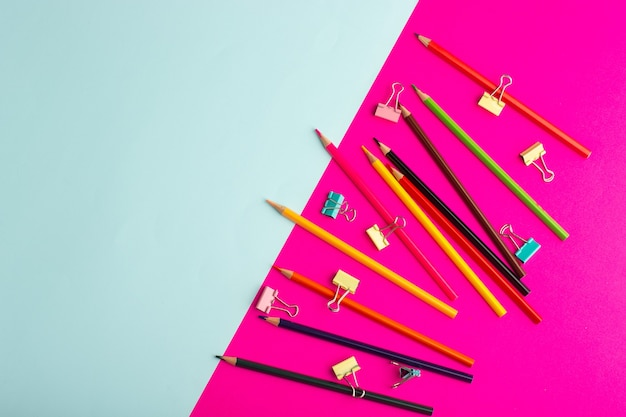 Top view colorful pencils with stickers on ice blue and pink wall color pencil pen drawing paint