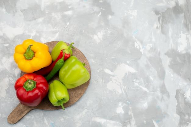 Peperoni variopinti di vista superiore con i peperoni dolci sullo scrittorio grigio