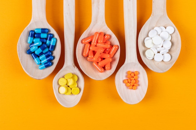 Top view of colorful pills in wooden spoons on orange background. horizontal