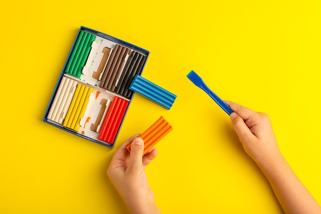 黄色の壁の色の写真の子供の学校で働いて遊んでいる上面図カラフルなプラスチックの子供