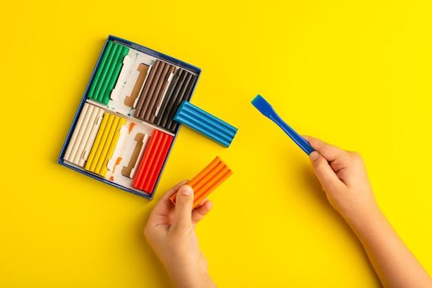 Vista dall'alto di plastiline colorate bambino che lavora e gioca con esso sulla scuola per bambini con foto a colori parete gialla