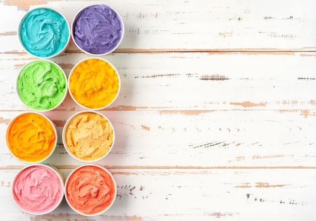 Top view of colorful rainbow ice cream in cups. copy space