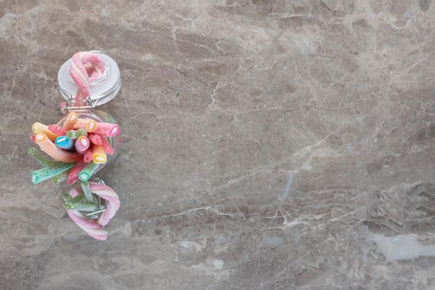 Vista dall'alto di caramelle colorate a nastro in barattolo su sfondo grigio.