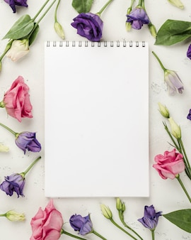 Top view colorful roses beside notebook