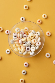 Top view of colorful round candy in transparent bowl