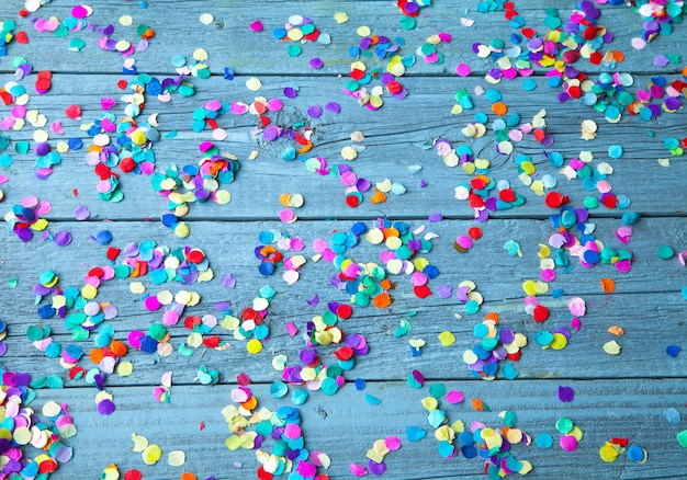 Top view of colorful round confetti on a light blue wooden background