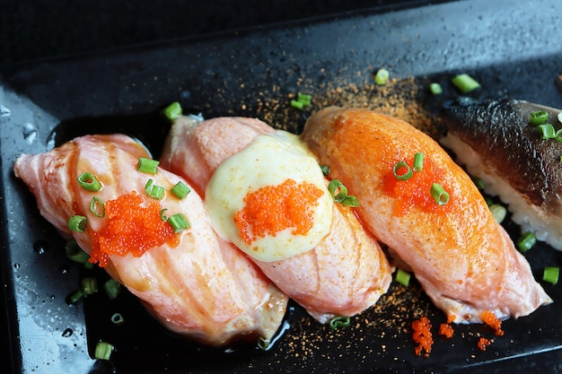 Top view colorful salmon sushi with tobiko eggs on top.