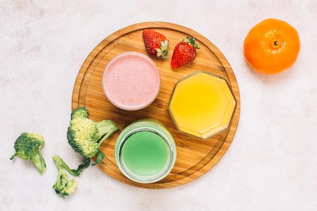 Вид сверху разноцветных смузи рядом с фруктами