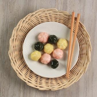 Вид сверху красочного сонгпён ккультток (рисовый пирог с медовой начинкой) в деревянной тарелке. сонпхён - это традиционная корейская еда, которую едят в новый год или в день корейской благодарности.