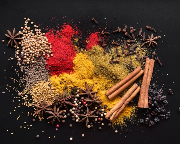 Top view colorful spices on black background