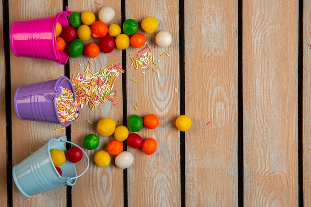 Top view of colorful sprinkles and candies scattered from small buckets