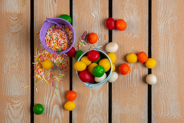 Top view of colorful sprinkles and candies in small buckets
