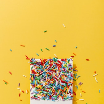 Top view of colorful sprinkles on photo with copy space
