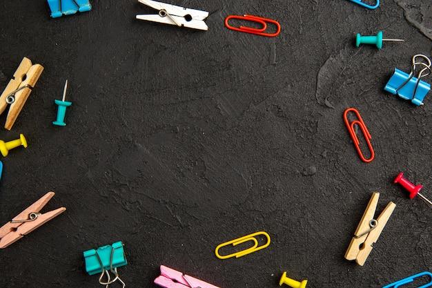 暗い背景の洗濯バサミとトップビューカラフルなステープルランドリーカラー写真学校の子供