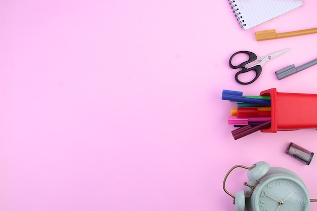 Top view of colorful stationery isolated on a pink background