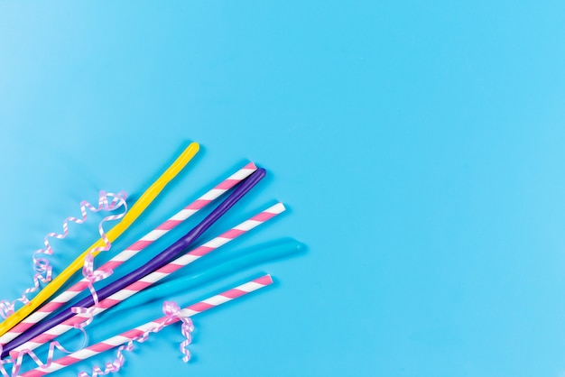 A top view colorful straws long sticky isolated on blue, drink juice cold color
