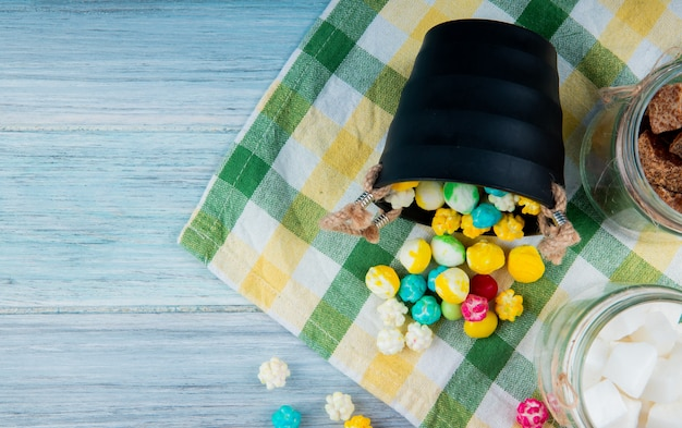 Top view of colorful sugar candies scattered from a bucket on plaid table napkin on rustic background with copy space
