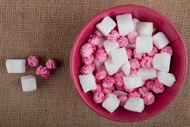Top view of colorful sugar candies with sugar cubes in a bowl on sackcloth texture background