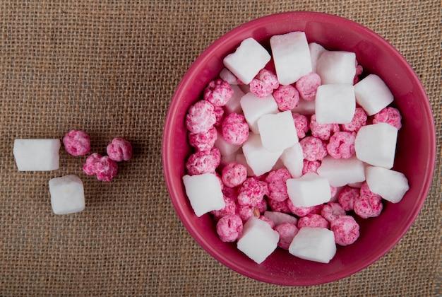 Vista superiore delle caramelle di zucchero variopinte con i cubetti di zucchero in una ciotola sul fondo di struttura della tela di sacco