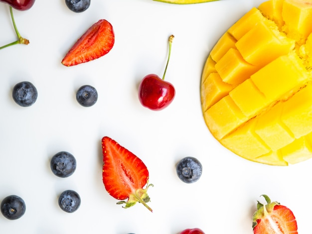 Top view colorful summer fruits. flat lay with mango, strawberry, and cherry on white background