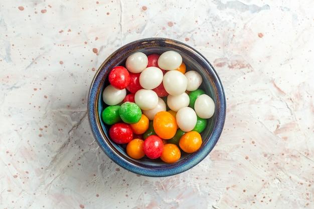 Vista dall'alto caramelle dolci colorate all'interno del piatto sullo zucchero candito dolce di colore bianco della tavola
