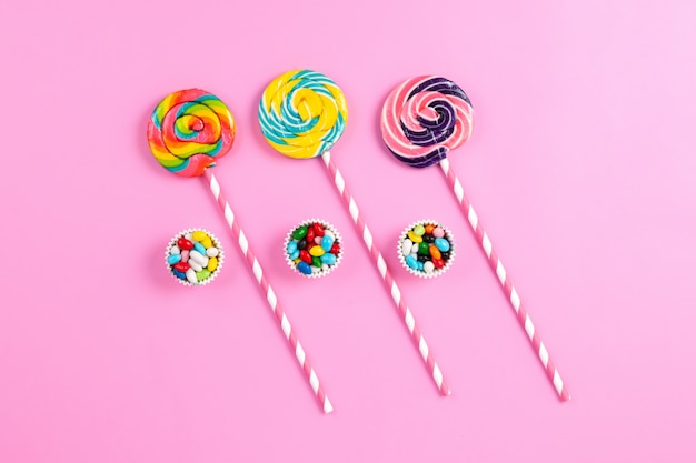 Una vista dall'alto lecca-lecca dolci colorati sui bastoncini di zucchero bianco-rosa e caramelle multicolori sull'arcobaleno di compleanno di sfondo rosa