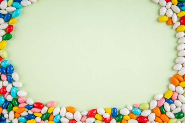 Top view of colorful sweet sugar candies on white background with copy space