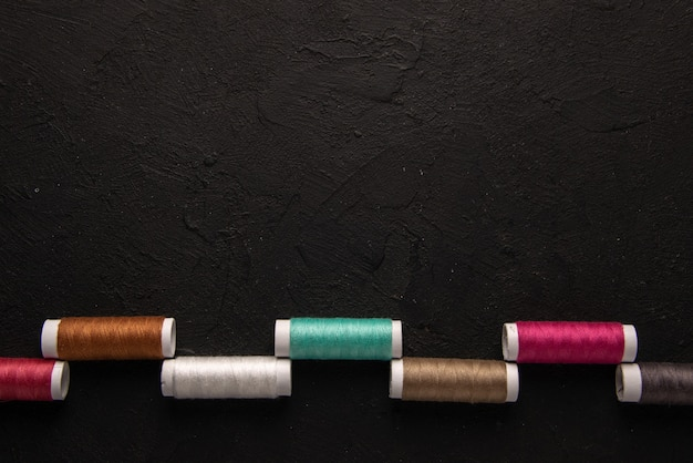 Top view of colorful threads on a dark wall
