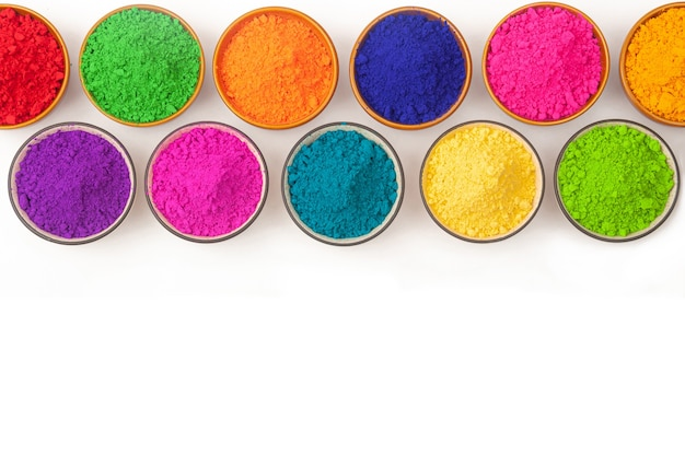 Top view of colorful traditional happy holi powder in bowls on white