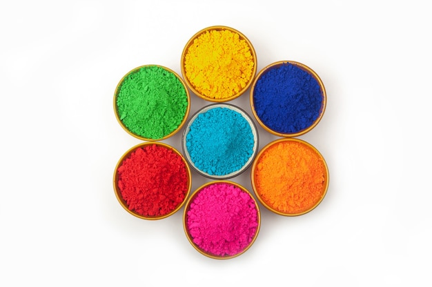 Top view of colorful traditional holi powder in bowls on white