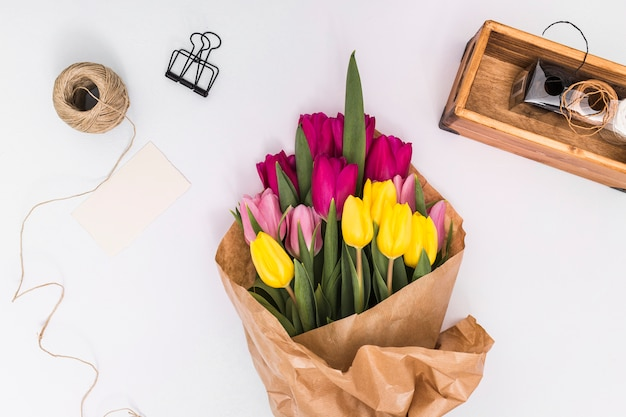 Top view of colorful tulip flowers; string; paper clip; card and brown paper above white surface