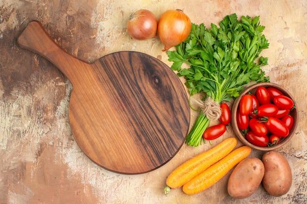 Vista dall'alto verdure colorate e un tagliere per la preparazione di insalata fresca su uno sfondo di legno con spazio per le copie