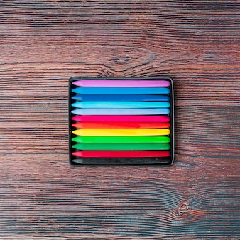 Top view of colorful wax crayons on wooden table