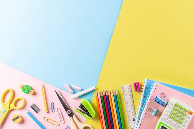 Top view of colourful school supplies, stationary on pastel paper.